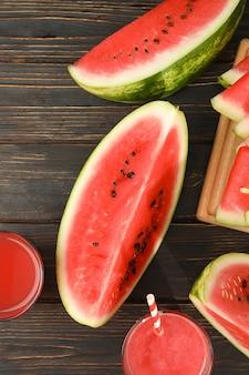 Kompozycja z kawałkami arbuza i soku na drewnianym. letni owoc