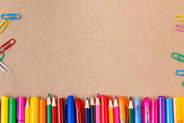 Kompozycja z kolorowych ołówków, markerów i długopisów z miejsca na kopię. powrót do szkoły koncepcja karton kraft