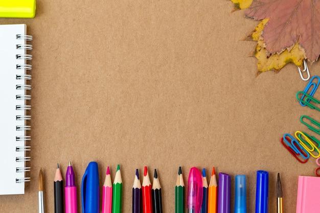 Kompozycja z kolorowym ołówkiem pustej strony notesu, markerem i piórem na tekturze rzemieślniczej. powrót do koncepcji szkoły