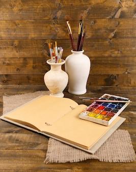 Kompozycja z kolorowymi akwarelami, pędzlami w wazonie i szkicownikiem na drewnianym