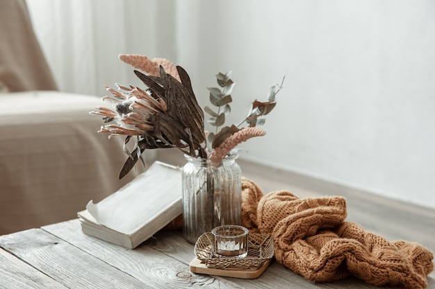 Kompozycja z książką, suchym kwiatkiem i dzianinowym elementem we wnętrzu pokoju