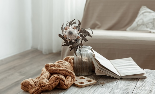 Kompozycja z książką, suchym kwiatkiem i dzianinowym elementem we wnętrzu pokoju.