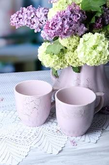 Kompozycja z kubków do herbaty i pięknych wiosennych kwiatów w wazonie, na drewnianym stole, na jasnym tle