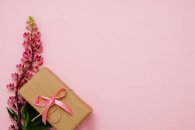 Kompozycja z kwiatami i prezentem na różowo