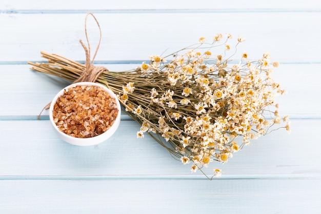 Kompozycja z kwiatów rumianku i domowego kosmetyku, olejku eterycznego, sopa, widok z góry