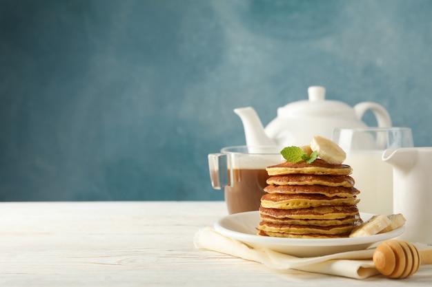 Kompozycja z naleśników, mleka i napój kakaowy na drewnianym stole. słodkie śniadanie