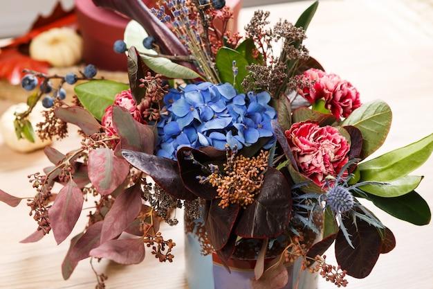 Kompozycja z niebieskiej pelargonii, suchych kwiatów i liści.