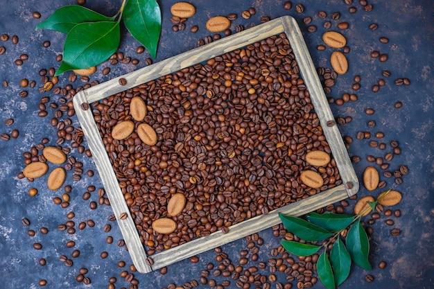 Kompozycja z palonych ziaren kawy i ciasteczek w kształcie ziaren kawy na ciemnobrązowej powierzchni