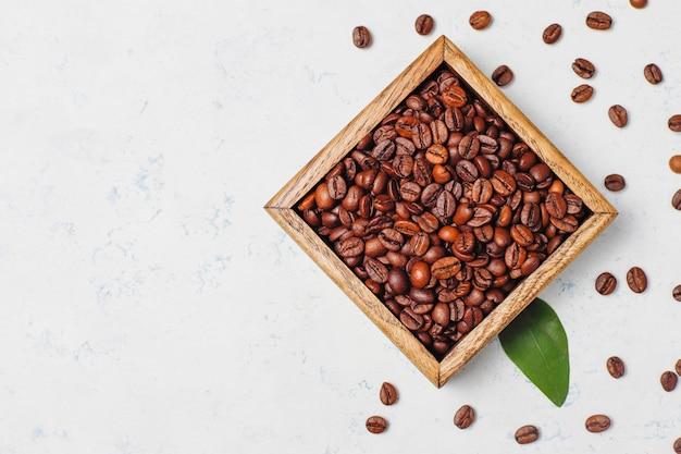Kompozycja z palonych ziaren kawy i ciasteczek w kształcie ziaren kawy na lekkiej powierzchni