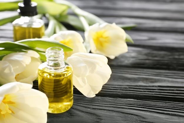 Kompozycja z perfumami i kwiatami na drewnianym stole