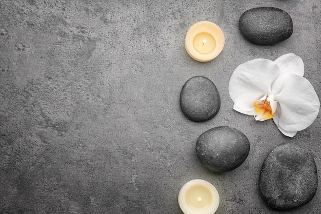 Kompozycja z piękną białą orchideą i kamieniami na szarym tle