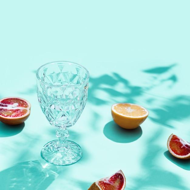 Kompozycja z plasterkami grejpfruta, czerwonej pomarańczy, cytryny i kieliszka do napojów.