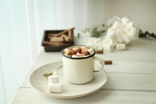 Kompozycja z pysznym kakao i pianką marshmallow na drewnianym stole