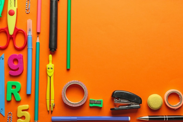 Kompozycja z różnymi szkolnymi papeteriami na pomarańczowo