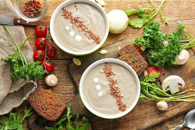 Kompozycja z smaczną zupą grzybową na drewnianym stole