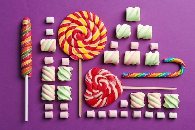 Kompozycja z smacznymi słodyczami na fioletowym, widok z góry