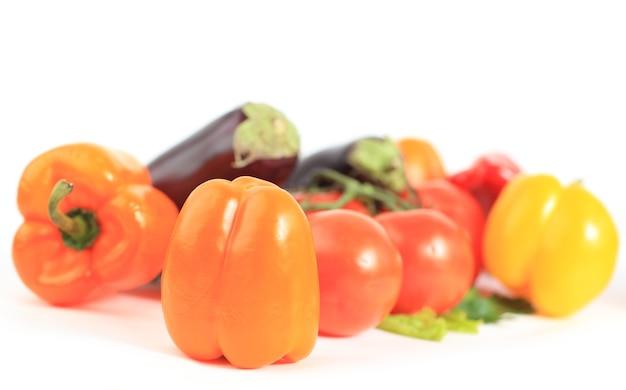 Kompozycja z surowymi warzywami i wiklinowym koszem na białym tle
