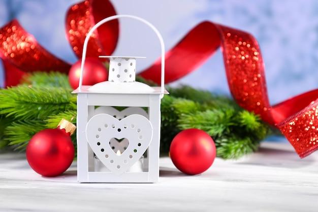 Kompozycja z świąteczną latarnią, jodłą i dekoracjami na jasnym tle