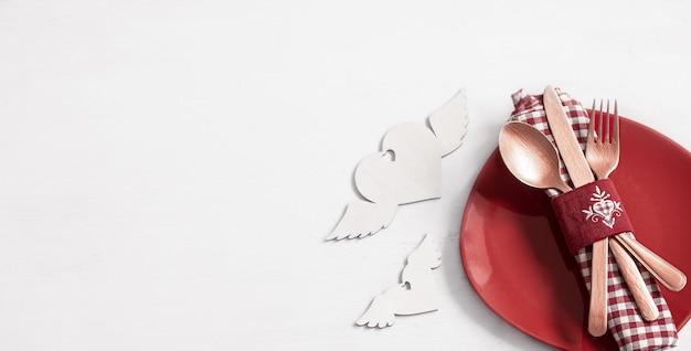 Kompozycja z talerzem i sztućcami na romantyczną kolację z widokiem z góry na walentynki. koncepcja randki.