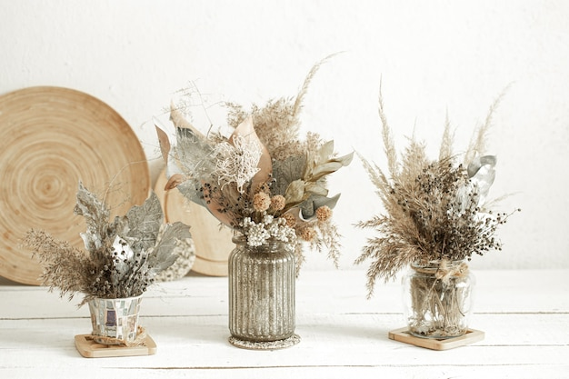 Kompozycja z wieloma suszonymi kwiatami w wazonach.
