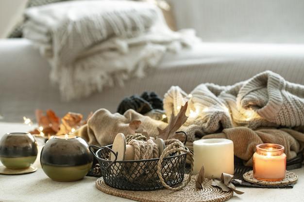 Kompozycja z wieloma świecami, ozdobny sznurek na przestrzeni pokoju w ciepłych kolorach.