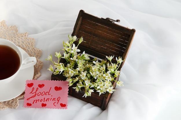 Kompozycja z wiosennymi kwiatami i filiżanką herbaty na białej satynowej ścianie