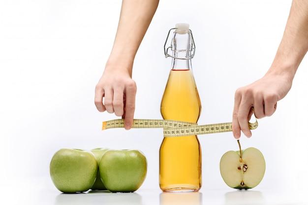 Kompozycja z zielonymi jabłkami, butelką soku jabłkowego i miernikiem krawieckim w rękach izolowanych z miejscem na tekst.