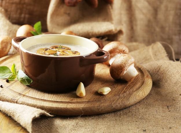 Kompozycja z zupą grzybową w garnku, świeżymi i suszonymi grzybami, na drewnianym stole, na worze