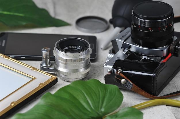 Kompozycja zdjęć - zabytkowa kamera filmowa, obiektywy, pusta ramka do zdjęć