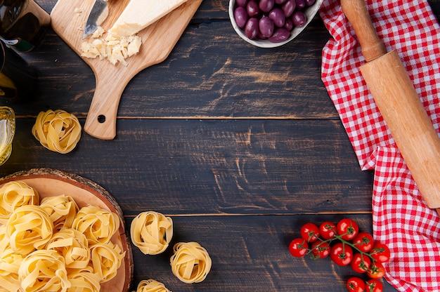 Kompozycja ze składnikami do przygotowania włoskiego makaronu. pomidory, parmezan, oliwki, bazylia i makaron surowy. miejsce na tekst