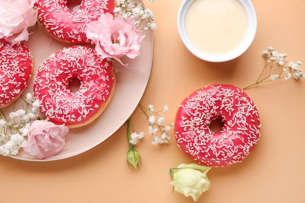 Kompozycja ze słodkimi smacznymi pączkami i kwiatami na kolor