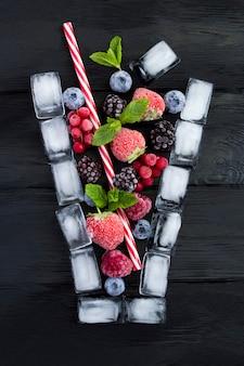 Kompozycja ze słomką koktajlową, mrożoną jagodą i lodem. widok z góry.
