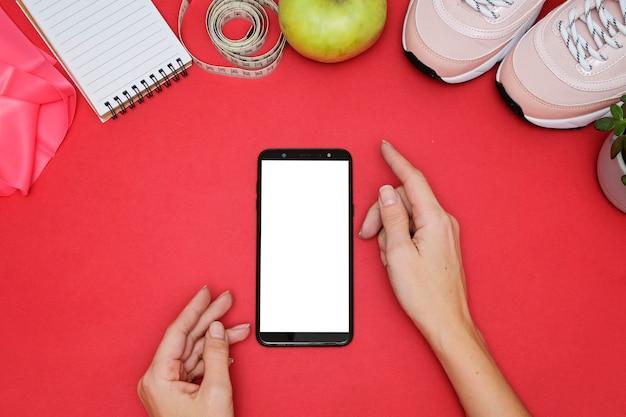 Kompozycja ze smartfonem i sprzętem sportowym. trampki, centymetrem, glukometr na czerwono