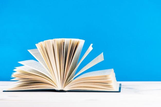 Kompozycja ze starą książką w twardej oprawie, pamiętnikiem, wachlowanymi stronami na drewnianym stole pokładowym. powrót do szkoły. edukacja
