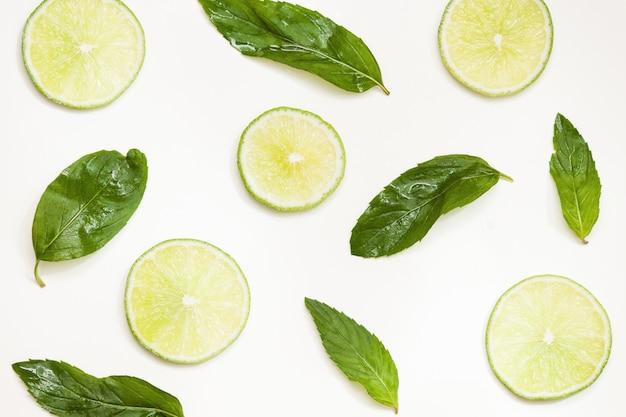 Kompozycja ze świeżych limonek, liści mięty na jasnym tle, widok z góry, zbliżenie.