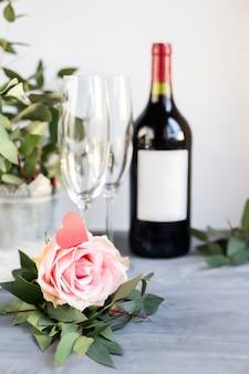 Kompozycja ze szkła, kwiatów i butelki winorośli na szarym tle betonu.
