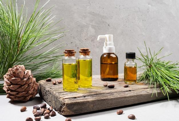 Kompozycja zestawu małych szklanych buteleczek olejku cedrowego na starej desce z gałązkami cedru, szyszką i orzechami na szaro. ziołolecznictwo, koncepcja iglaste spa. skopiuj miejsce. zdjęcie poziome.