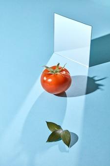 Kompozycja zielonych liści soczystego pomidora i lustra