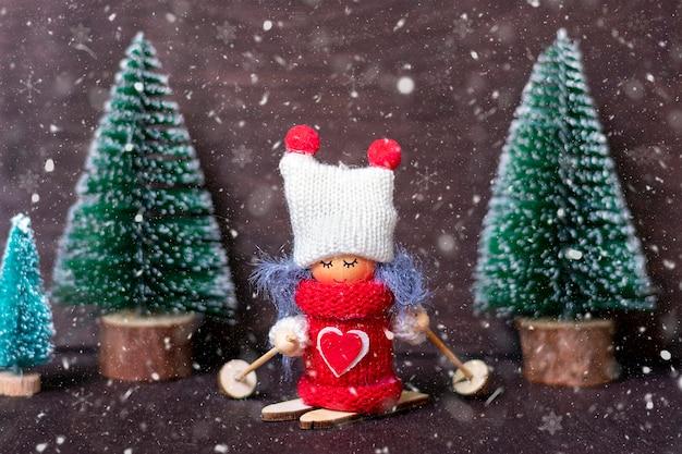 Kompozycja zimowa dziewczyna na nartach w czerwone ubrania i biały kapelusz, choinka na drewnianym tle