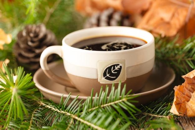 Kompozycja zimowa. filiżanka kawy, sosnowe gałąź na drewnianym stole.