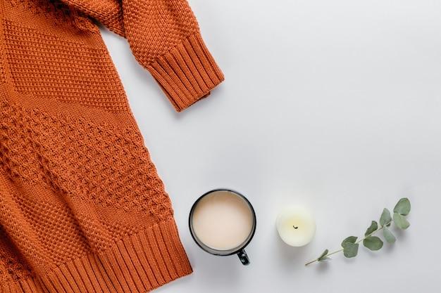 Kompozycja zimowa. pomarańczowy sweter, świece i gałąź eukaliptusa