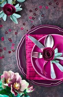 Kompozycja złożona z talerzy i naczyń ozdobionych różami z papieru w kolorze magenta