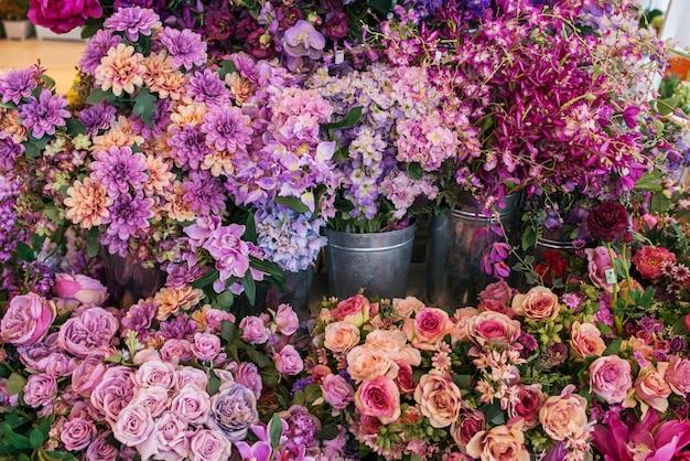 Kompozycje różowych i fioletowych kwiatów w metalowych kostkach