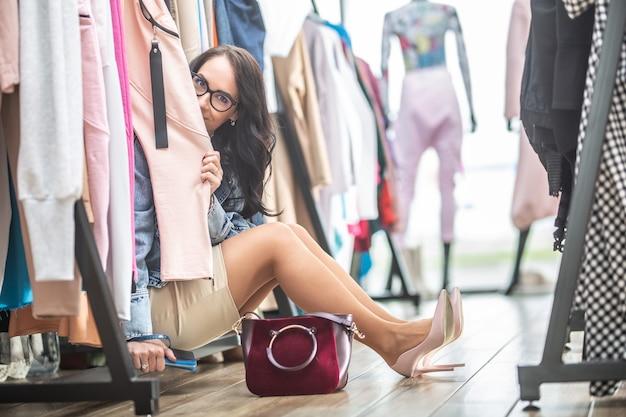 Kompulsywna, nieładna kobieta w spódnicy i dżinsowej bluzce siedzi wśród ubrań w sklepie z modą.