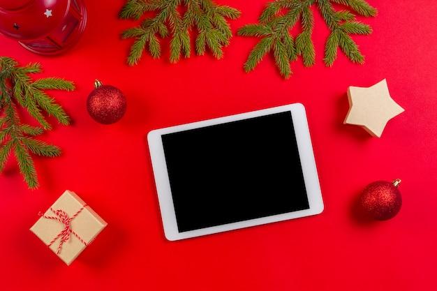 Komputer cyfrowy typu tablet makiety na czerwonym tle na czas bożego narodzenia.