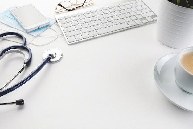 Komputer, fonendoskop i kawa na białym stole. biurko lekarskie.