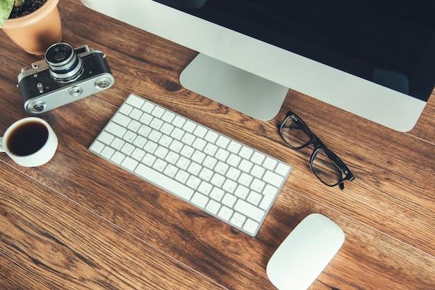 Komputer i kawa z aparatem na biurku