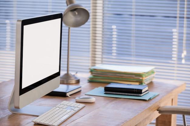 Komputer i książki na biurku
