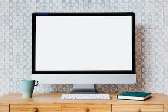 Komputer, klawiatura, kubek i pamiętnik nad drewnianym biurku