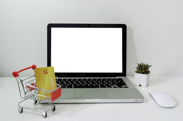 Komputer laptop makieta pusty biały i koszyk i karta kredytowa na biurku. służy do umieszczania tekstu lub informacji w celu reklamowania wiadomości lub sprzedaży produktów online. biznes marketingowy koncepcyjny